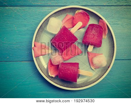 Fruity red water ice on a blue plate