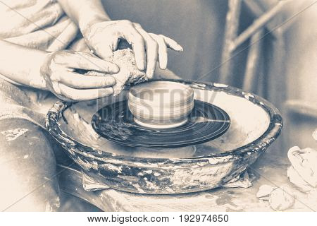 person potter makes clay jug on a potter's wheel in pottery workshop
