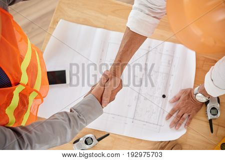 Firm handshake of contractor and head engineer