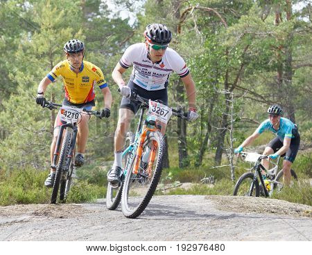 STOCKHOLM SWEDEN - JUNE 11 2017: Group of mountain bike cyclists in the forest in a curve at Lida Loop Mountain bike Race. June 11 2017 in Stockholm Sweden