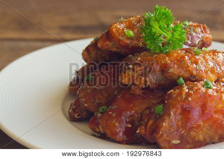 Barbecue chicken wings on white plate served with barbecue dipping sauce. Homemade bbq chicken wing delicious moist and spicy. Barbecue chicken wing ready to served on wood table.