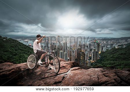 Man with bycicle up to the hill far from a vetical city