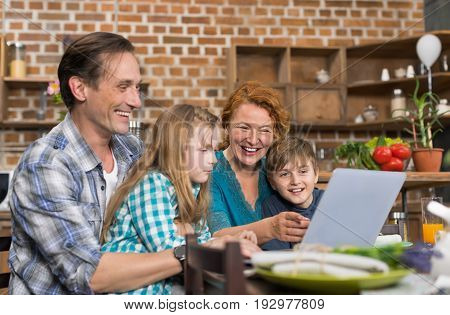 Happy Family Use Laptop Computer Sitting At Kitchen Table, Parents With Son And Daughter Surfing Internet Before Cooking Food