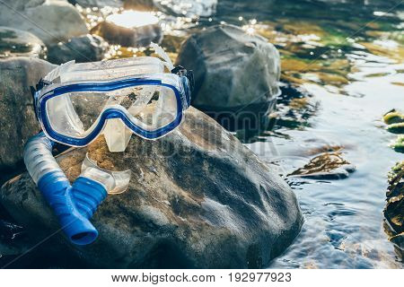 Diving Mask And Snorkel Lie on The Stones On The Sandy Closeup. Tourism Travel Freediving Concept