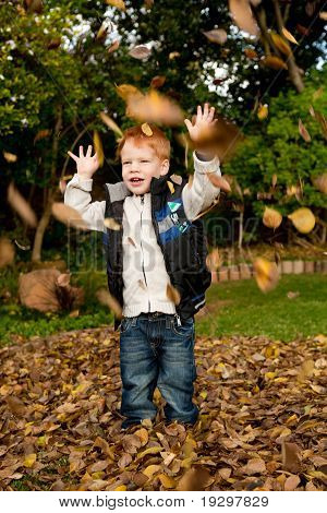 Happy red haired young boy playing and throwing leaves into autumn air in a park
