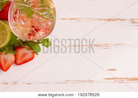 Top view strawberry lemon lime mojito in clear glass on rustic wood table. Infused water: strawberry soda made with strawberry lemon or lime and mint leaf with copy space for background or wallpaper.