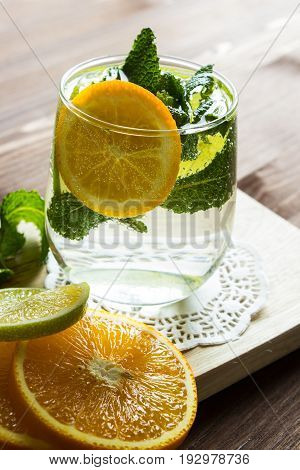 Cold lemonade with orange and mint in a glass cup on a wooden stand. Selective focus. Top view.