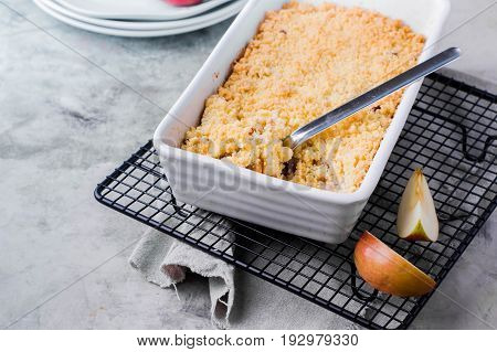 Apple crumble in white ceramic form on gray table background. Fruit pie on grate for cooling