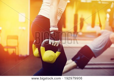 Close-up girl is Training with a dumbbell in the gym.concept of fitness