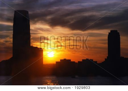 Skyline And Skysrapers With Water And Setting Sun