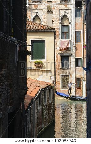VENICE, ITALY - CIRCA 2013: The historic city of Venice with its ancient buildings on canals and a typical gondola