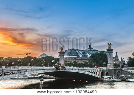 Sunset with Alexander III bridge, Great Palace and the Seine river in Paris, France