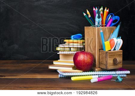 School supplies and accessories on wooden table over blackboard background