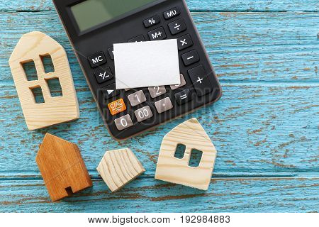 Calculator And Wood Houses On Wood Background