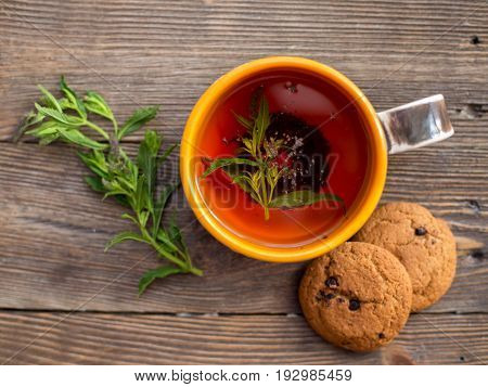 Cup of tea with mint and cakes. Teatime - relax with hot black tea. Aromatic black tea brewed in cup. A cup of black tea with mint on a wooden surface.