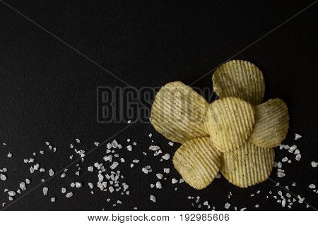 Crinkle cut potato chips on a chalkboard. Tasty spicy potato chips with salt.Top view