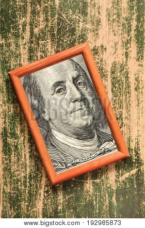 Benjamin Franklin 100 USA dollar portrait in a wooden photo frame