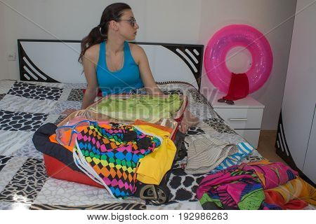 Woman packing preparing for summer vacation. Travel concept. Young Girl packing suitcase on bed at home