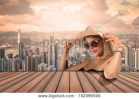 gilr with sunglasses and hat on a tall city view