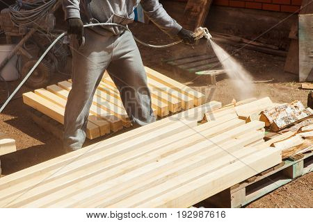 Application of flame retardant to ensure fire protection, airless spraying device. Woodworker clean the plank from shavings in workshop. Carpenter coating cuttings from wooden bar.