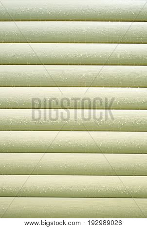 Wall covered with horizontal beige siding panels, protect building from bad weather conditions as background front view vertical photo closeup