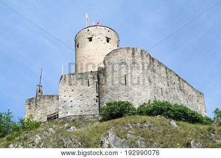Marigny, Switzerland - 4 April 2013: Ancient castle with cylindrical tower of Martigny on the Swiss alps