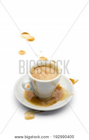 full cup of coffee with coffee spilled on the saucer and on the white table.