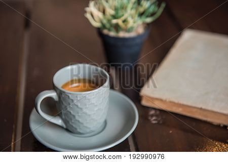 Cup coffee on White wooden table and old book and pot .