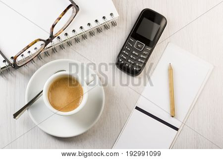 cup of coffee on white office table with notes pencil phone and eyeglasses.
