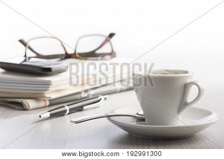 steaming cup of coffee on white office table with notes phone eyeglasses and ball pen on background.