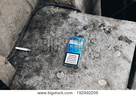 BRISTOL UNITED KINGDOM - MAR 8 2017: Mayfair cigarette pack thrown on the asphalt with large warning test: Smoking may reduce the blow flow and cause impotence