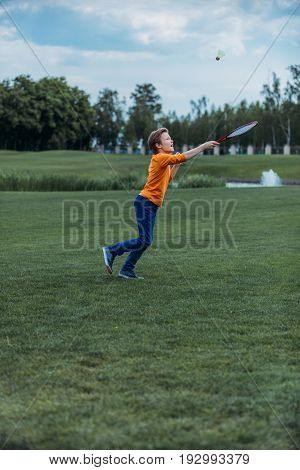 Caucasian Boy Playing Badminton With Racquet And Shuttlecock, On Green Field