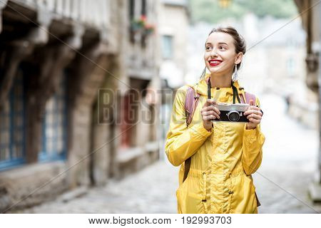 Young woman in yellow raincoat walking with backpack and photo camera in Dinan village at Brittany region in France