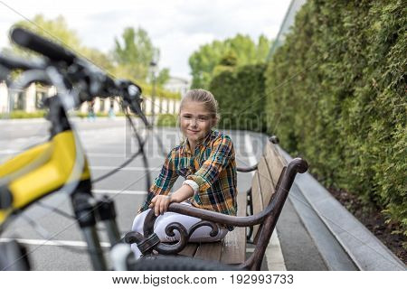 smiling pre-adolescent girl looking at camera while sitting on bench at park