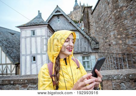 Young woman in yellow raincoat using smart phone on Mont Saint Michel island in France