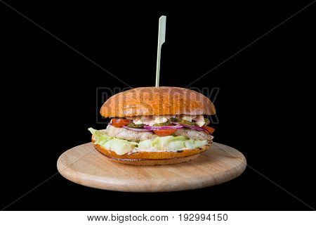 Big beef burger on wooden board isolated on black