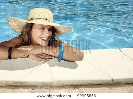 smiling and charming blonde girl with straw hat in a swimming pool