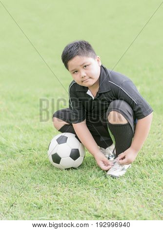 Obese Boy Tying His Football Shoes, Healthy Concept
