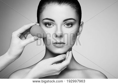 Makeup artist applies skintone. Beautiful woman face. Perfect makeup. Skincare foundation. Sponge makeup artist. Black and White photo