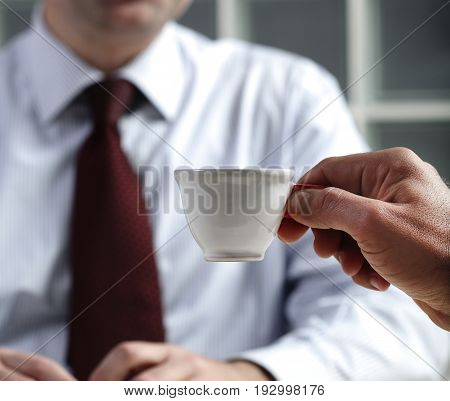 close up photo of a hand holding an expresso coffe in a team meeting
