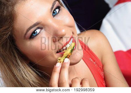 Close up photo of a gilr biting pineapple