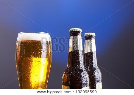 Close up of glass of light beer and two beer bottles