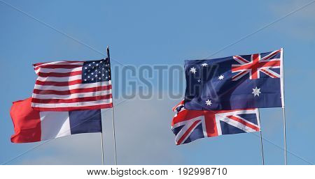 Four National Country Flags Flying on a Sunny Day.