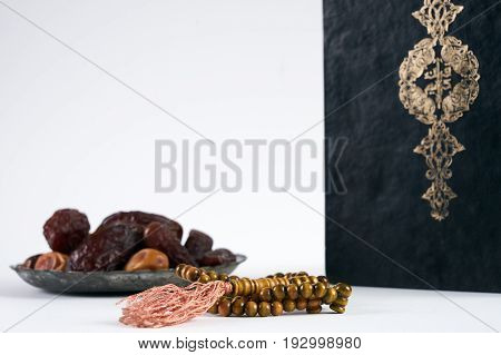 Islamic Holy Book Quran/ Kuran With wooden prayer beads Rosary and dry Dates Over white Background with copy space