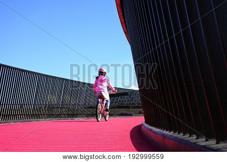 Young girl (age 07) rides a bike on a bright pink cycleway in Auckland New Zealand. Real people Copy space.