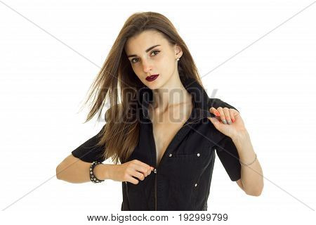 Portrait of a beautiful young girl with hair by air which unzips her jacket and looks into the camera, isolated