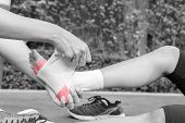 Young woman runner ankle being applied bandage by man in park. injury ankle - black and white concept poster