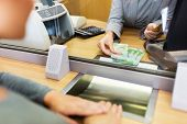 people, withdrawal, money, saving and finance concept - clerk counting swiss francs cash at bank office or currency exchanger poster
