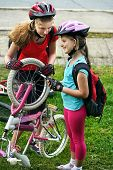 Bicycle tire pumping by child bicyclist. Girl repair bicycle on road . Kids pump up tire. Children return home from school on bicycles. Tone image. poster