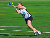 High school girls lacrosse player has her eye on the ball as it rolls out of her stick. poster